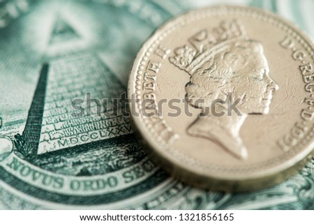 British Sterling Pound and American Dollar currency. Sterling Pound coin on an American one Dollar bill. #1321856165