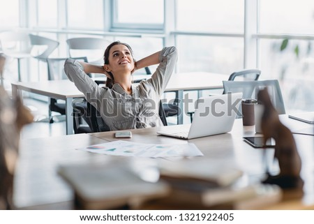 Happy businesswoman relaxing with hands behind head at office desk. Daydreaming concept #1321922405