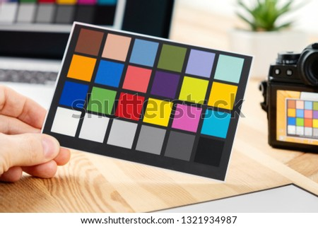 Man holds a paper card with test colors for color management and profiling. Equipment for adjust and balance photograph. Camera and laptop on background.