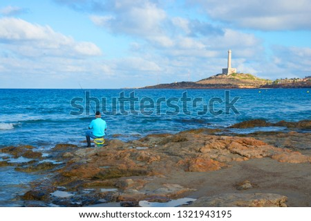 Cabo de Palos, Murcia, España- 13 October 2018.  A fisherman on the shore of the beach in front of the lighthouse of Cape de Palos #1321943195