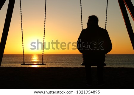 Back view backlighting silhouette of a man alone on a swing looking at empty seat at sunset on the beach in winter #1321954895