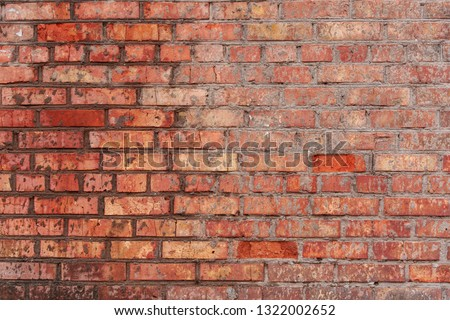 The wall is of red brick with natural defects: faults, cracks, chips, scratches, crevasses, roughness. Horizontal masonry. Part of the old wall. Could be used as background for design. #1322002652