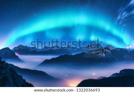Aurora borealis above mountains in fog at night. Northern lights. Sky with stars with polar lights and high rocks. Beautiful landscape with aurora, city lights in low clouds, mountain ridge. Space #1322036693