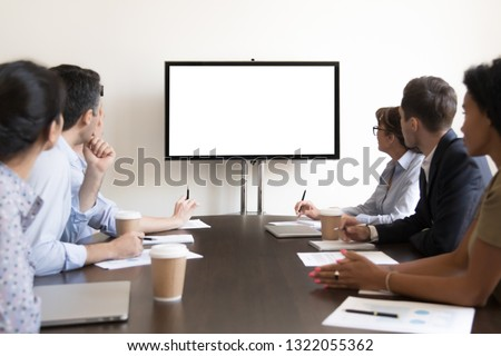 Business executive people group sitting at conference table looking at white blank mockup tv screen on wall watching presentation in meeting room, company training corporate team seminar in boardroom #1322055362
