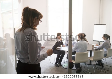 Stressed nervous stuttering inexperienced businesswoman standing at office door feeling afraid worried before performance reading paper preparing business speech, public speaking fear anxiety concept #1322055365
