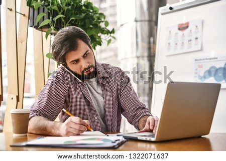 Success is the sum of small efforts – repeated day in and day out. Horizontal shot of male office worker making notes with pen in his notebook at co-working space. #1322071637