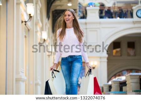 Young beautiful blonde woman with some shopping bags in the mall #1322074076