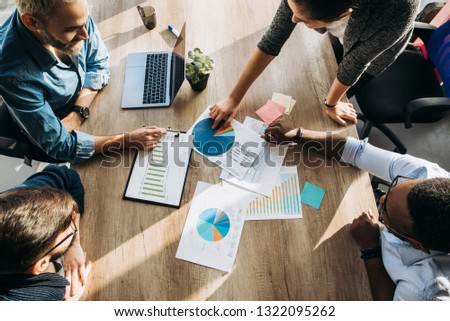 Busy working day. Top view of young modern people in stylish casual wear they talking about business while working in the creative office Royalty-Free Stock Photo #1322095262