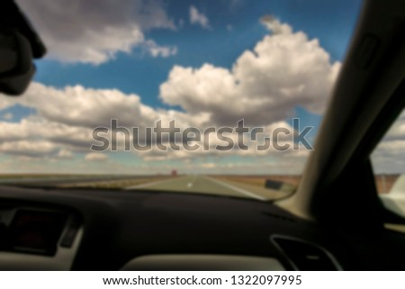 Blurred background image Travel journey from a car cockpit. Driving car on highway. Concept of adventure trip to beautiful landscape with clouds #1322097995