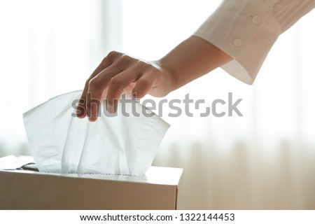 women hand picking napkin/tissue paper from the tissue box Royalty-Free Stock Photo #1322144453