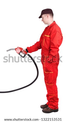 Man gas station staff  is holding red gasoline pistol pump fuel nozzle                                #1322153531