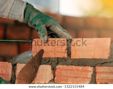 Construction worker installing bricks in construction site #1322155484