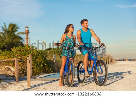 Florida beach vacation couple biking sport rental bikes recreational activity happy watching sunset on Sanibel Island by the Lighthouse. Young woman and man riding bicycles. Summer people lifestyle . #1322166806
