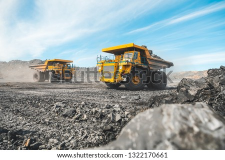 Large quarry dump truck. Loading the rock in dumper. Loading coal into body truck. Production useful minerals. Mining truck mining machinery, to transport coal from open-pit as the Coal Production #1322170661