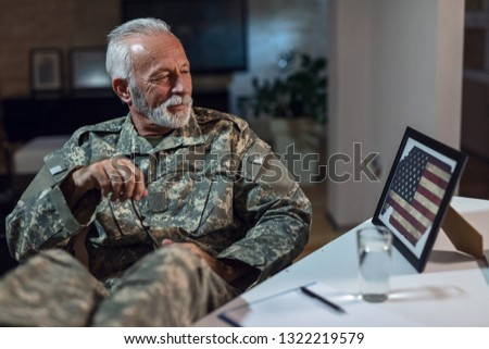Smiling mature army soldier feeling proud and admiring the American flag in picture frame while relaxing in the office.