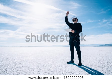 Full length view of young male Interacting with digital virtually world standing outdoors with spacious landscape copy space.Future innovative technology,man in VR headset creating details with pencil #1322222003