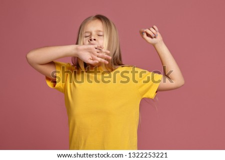 little girl in a yellow t-shirt. stretches and yawns #1322253221