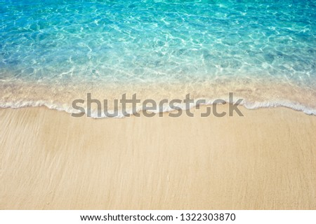 Soft blue ocean wave on clean sandy beach #1322303870