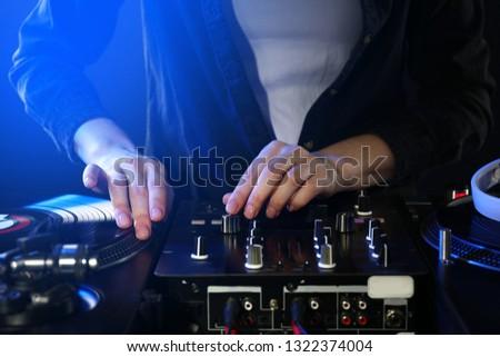 Female DJ mixing music, closeup #1322374004
