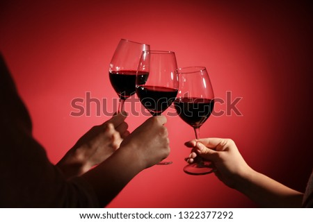 Women clinking glasses with tasty red wine on color background #1322377292