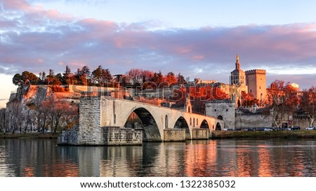 view of Pont Saint-Bénezet(Pont d'Avignon) and the medieval castle/walls in the sunset time in fall in Avignon, France. Pont Saint-Bénezet is famous for its history and the broken part in the river. #1322385032