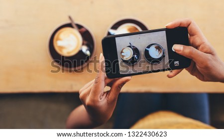 POV shot of woman photographing coffee cups on the cafe table with her smart phone. Female doing food photography with her mobile phone for her social media content.