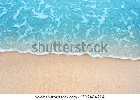 Soft blue ocean wave on clean sandy beach #1322464214