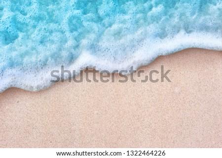 Soft blue ocean wave on clean sandy beach #1322464226