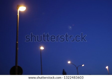 Streetlamps shining at a clear blue night sky #1322483603