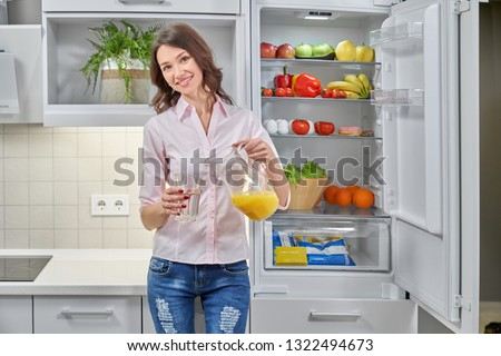 Beautiful, slender girl pouring fresh orange juice with pitcher in glass. Young woman standing near opened refrigerator with organic fruits, smiling, posing and looking at camera. #1322494673