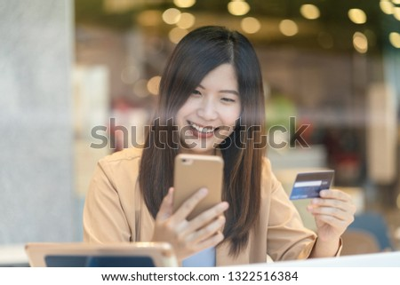 Portrait Asian woman using credit card with smart mobile phone for online shopping in department store over the clothes shop store background, technology money wallet and online payment concept #1322516384