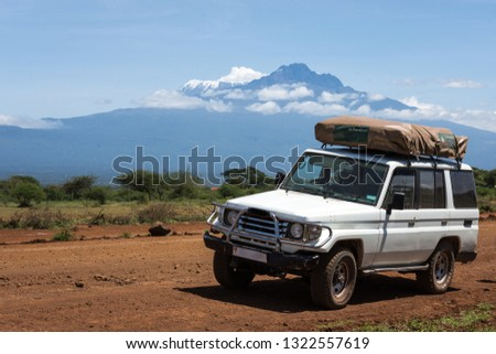 Jeep with a roof top tent in front of Kilimanjaro mountain on Mai 25th of 2017 #1322557619