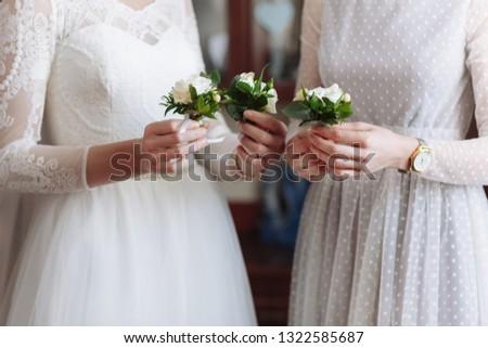 Beautiful wedding boutonier with white and green flowers in the hands of the bride and girlfriends in white dresess #1322585687