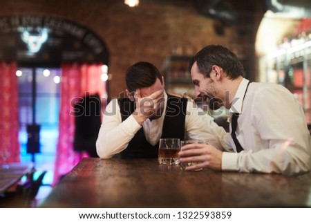Portrait of two drunk businesspeople sitting at bar counter after work, copy space #1322593859