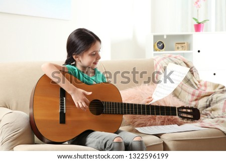 Cute little girl playing guitar on sofa in room #1322596199