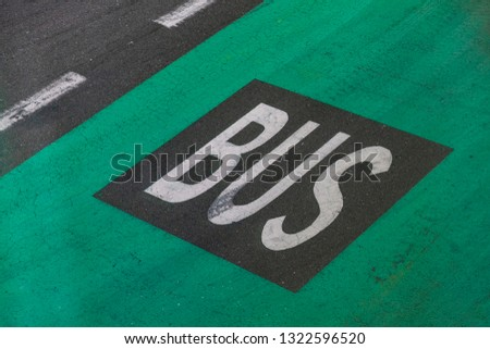 """Dedicated lane for buses at the airport. The word """"bus"""" is written in the asphalt white letters on a bright green background. Bus lane. #1322596520"""