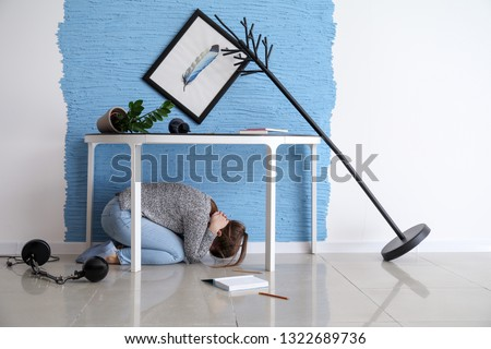 Young woman hiding under table during earthquake #1322689736