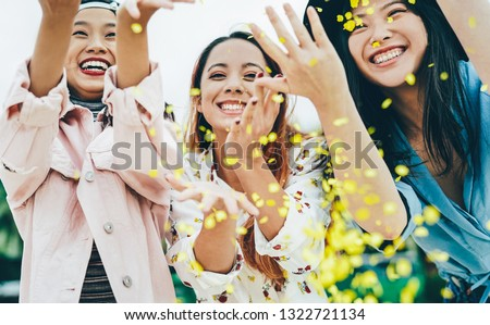 Happy Asian friends having fun throwing confetti outdoor - Young trendy people celebrating at festival event outside - Party, entertainment and youth holidays lifestyle concept  #1322721134