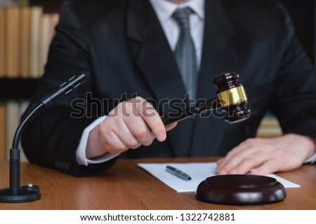 Law and order. Judge man with documents and gavel on the table. Court listens to condemn and punish. Execution of a court sentence.  Royalty-Free Stock Photo #1322742881