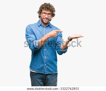 Handsome hispanic model man wearing glasses over isolated background amazed and smiling to the camera while presenting with hand and pointing with finger. #1322762855