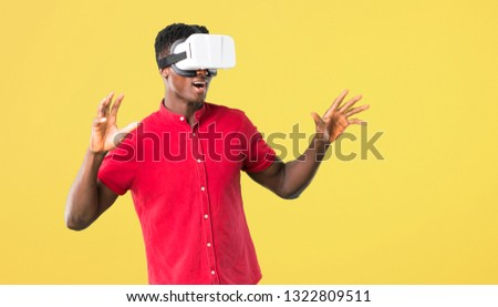 Young african american man using VR glasses. Virtual reality experience on yellow background #1322809511