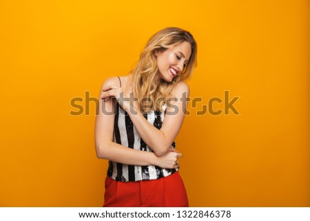 Portrait of a beautiful young blonde woman standing isolated over yellow background #1322846378