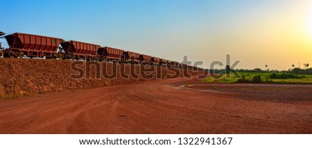 Railway carriages for transportation of bauxite ore on train tracks at the end of the railway line from bauxite mining. Guinea, Africa. #1322941367