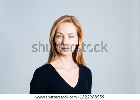 Close up studio portrait of a beautiful woman in the black dress against white background Royalty-Free Stock Photo #1322968559