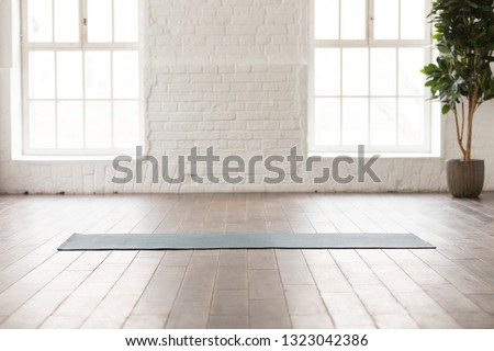 Yoga mat on natural wooden floor in empty room in fitness center, comfortable space for doing sport exercises, big windows and white brick walls, modern yoga class room with nobody #1323042386