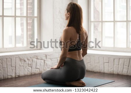 Beautiful woman in grey sportswear, leggings and bra practicing yoga, doing seiza exercise on mat, vajrasana pose, attractive sporty girl working out at home or in modern yoga studio, rear view #1323042422