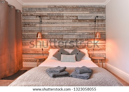 Modern Bedroom with rustic wooden headboard and white linen and pillows, copper lamp shade - Airbnb accommodation  #1323058055