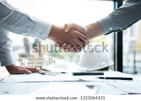Handshake of collaboration, Construction engineering or architect discuss a blueprint and building model while checking information on sketching, meeting for architectural project of partner. #1323064331