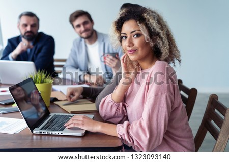 Beautiful business African lady is looking at camera and smiling while working in office. Attractive female manager sitting at desk #1323093140