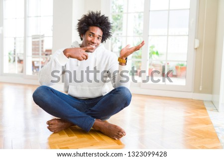 African American man sitting on the floor at home amazed and smiling to the camera while presenting with hand and pointing with finger. #1323099428